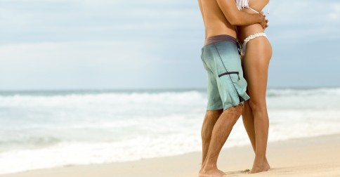 Attractive couple in embrace on sandy beach